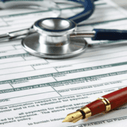 Stethoscope and pen above HIPAA compliance paperwork
